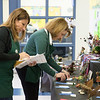 Pennsylvania Horticultural Society volunteer Renee Meister, left, and Junior Flower Show organizer Johanna Schoeller, right, place ribbons on contestants' entries.  Rachel Wisniewski — For Digital First Media