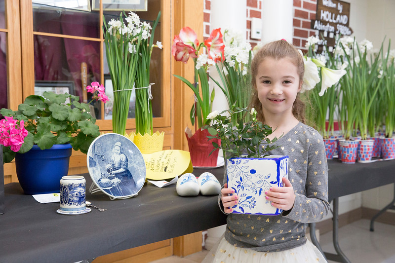 Kindergartner Annika Day, holding a Dutch-inspired flower vase, stands besides several Dutch relics that her family donated as visual aids to the school's Junior Flower Show.  Rachel Wisniewski — For Digital First Media