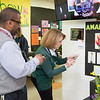 Junior Flower Show organizer Johanna Schoeller, right, joins Highland Elementary School Principal Jim Etlen in using their phones to photograph a QR code, a feature of LiAna Soltus' project on Amarylis flowers.  Rachel Wisniewski — For Digital First Media