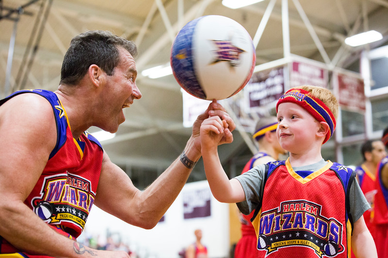 """Harlem Wizards player """"Blackjack"""" helps Brennan Oldham to spin a basketball on his finger at the close of the Wizards' game against Abington School District faculty and administrators at Abington High School April 8.  Rachel Wisniewski — For Digital First Media"""