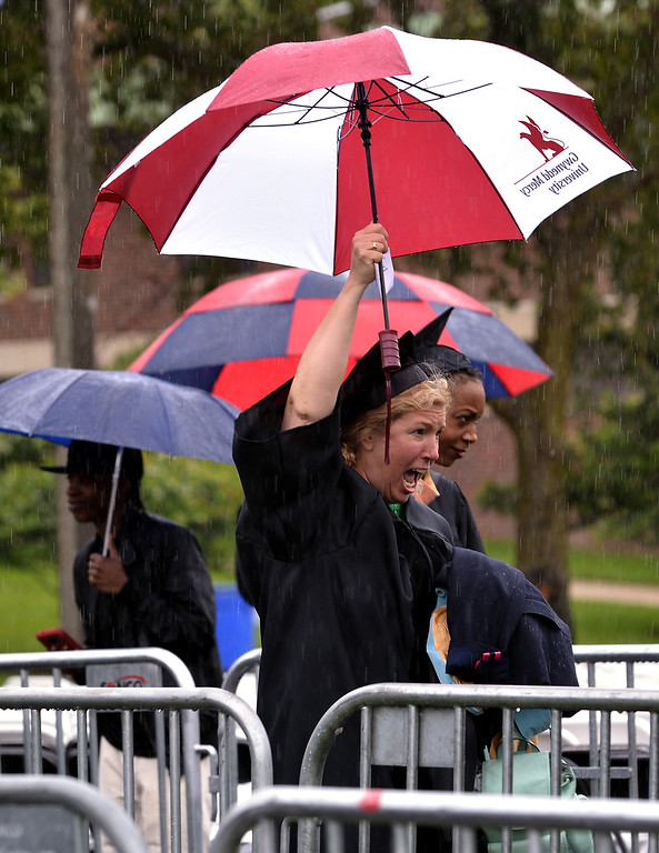 . At least one graduating student is undaunted by the pouring rain at the Gwynedd Mercy University commencement May 13, 2017.  (Bob Raines/Digital First Media)