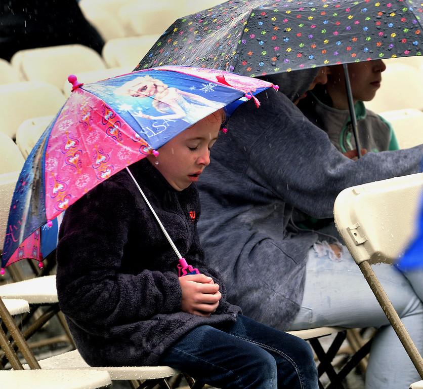 . This little girl looks cold and wet as she waits for the procession to end and the graduation to begin at Gwynedd Mercy University  May 13, 2017.  (Bob Raines/Digital First Media)