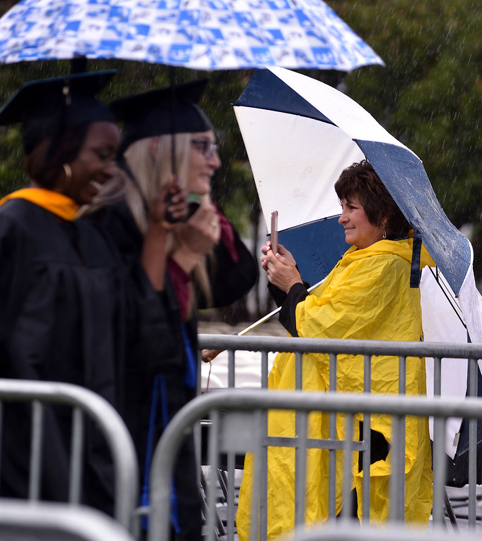 . A proud parent waits with cellphone camera ready during the procession at the Gwynedd Mercy University commencement May 13, 2017.  (Bob Raines/Digital First Media)