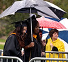 Two students share an umbrella during the procession at the Gwynedd Mercy University commencement May 13, 2017.  (Bob Raines/Digital First Media)