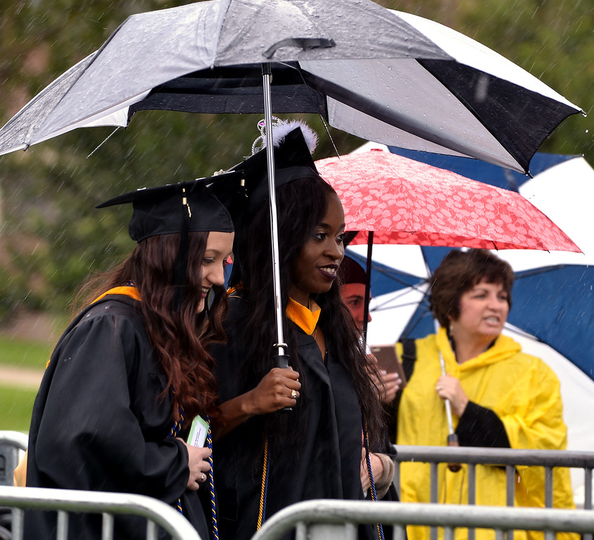 . Two students share an umbrella during the procession at the Gwynedd Mercy University commencement May 13, 2017.  (Bob Raines/Digital First Media)