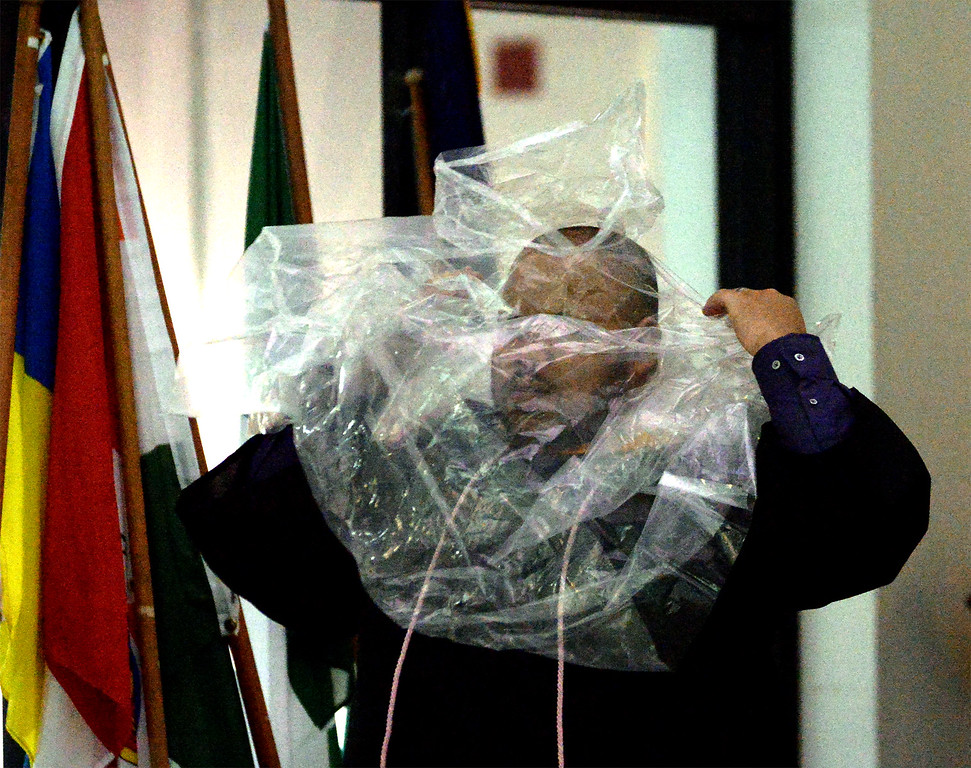 . Martyn Payne struggles into a clear plastic poncho as he prepares for his rainy graduation from Gwynedd Mercy University May 13, 2017.  (Bob Raines/Digital First Media)
