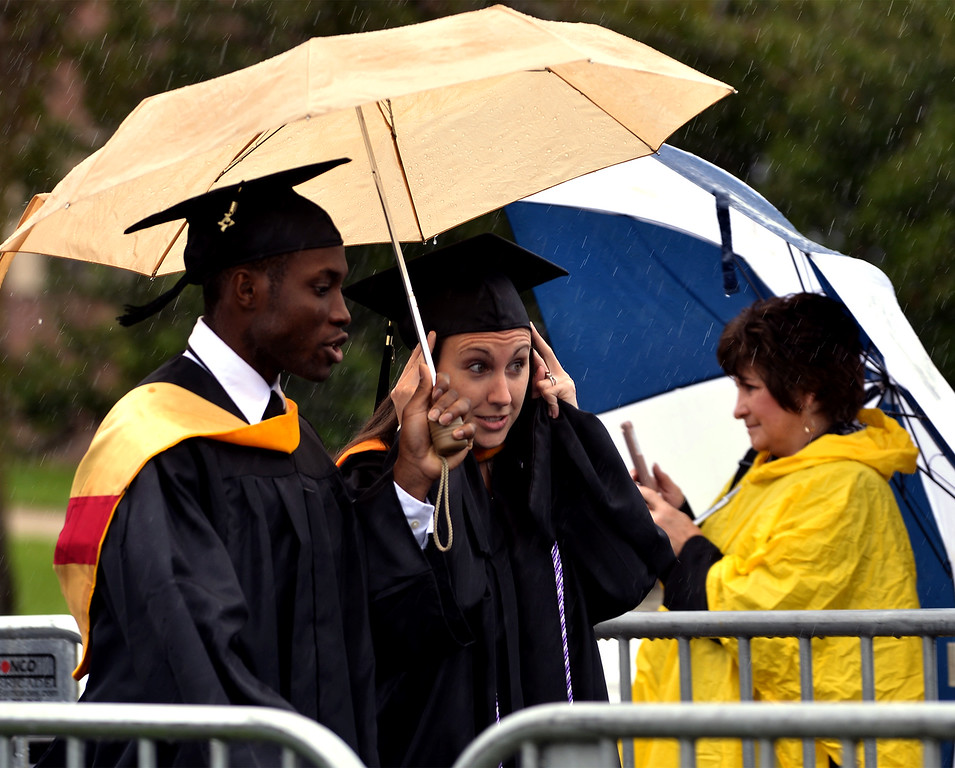 . Students share an umbrella during the procession at the Gwynedd Mercy University commencement May 13, 2017.  (Bob Raines/Digital First Media)