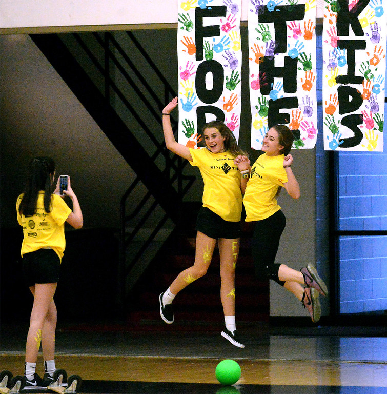 ". Ally Scott takes a photo of Rachel Carney and Sophia Boyer jumping in front of a ""For The Kids\"" sign at the Hatboro-Horsham High School miniTHON May 13, 2017.  (Bob Raines/Digital First Media)"