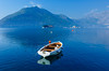 A boat reflected in the calm water of the Bay of Kotor near Perast, Montenegro.