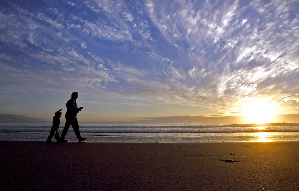 . People walk along Del Monte Beach in Monterey on Dec. 18, 2003.  (Vern Fisher - Monterey Herald)