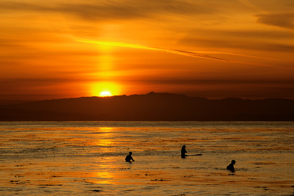 . Surfers bob in the surf as a colorful sunset breaks over Santa Cruz on Feb. 22, 1997.  (Vern Fisher - Monterey Herald)