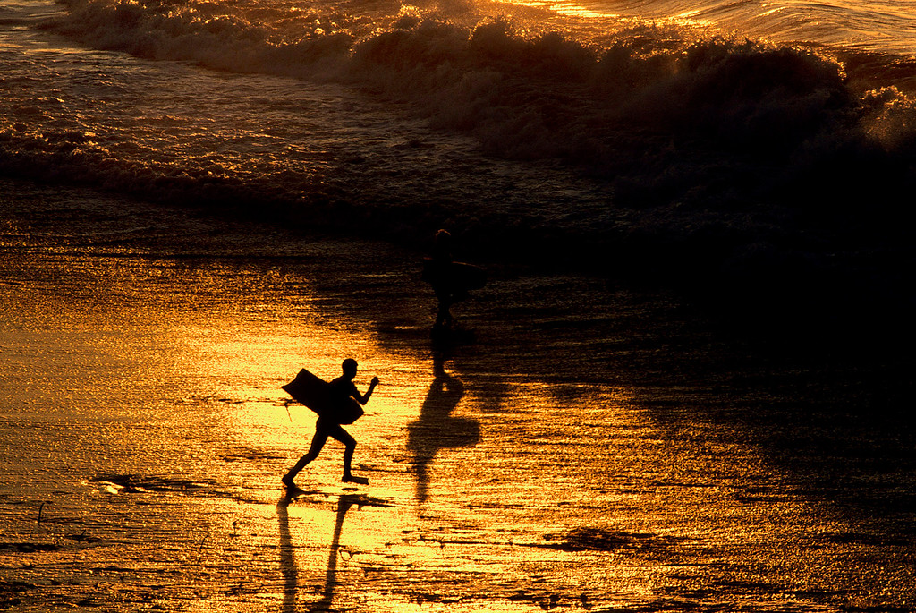 . A boogie boarder runs into the surf on the golden sands of It\'s Beach in Santa Cruz on Dec. 3, 2002.  (Vern Fisher - Monterey Herald)