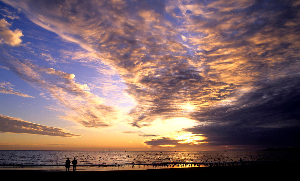 . People watch a colorful sunset at Marina State Beach on Oct. 23, 2002.  (Vern Fisher - Monterey Herald)