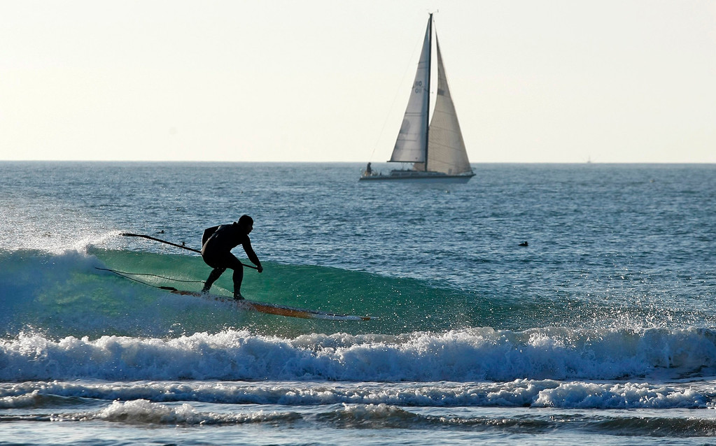 . A sailboat and paddle boarder at Moss Landing State Beach during a low tide of minus 1.1 feet on January 21, 2015.   (Vern Fisher - Monterey Herald)