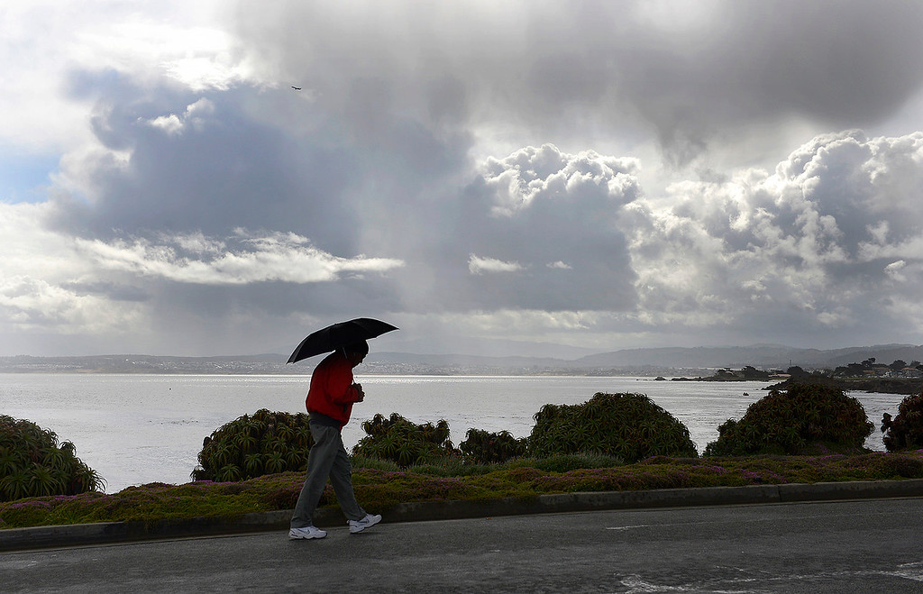 . A pedestrian uses an umbrella due to rain in Pacific Grove on Monday, April 16, 2018.  (Vern Fisher - Monterey Herald)