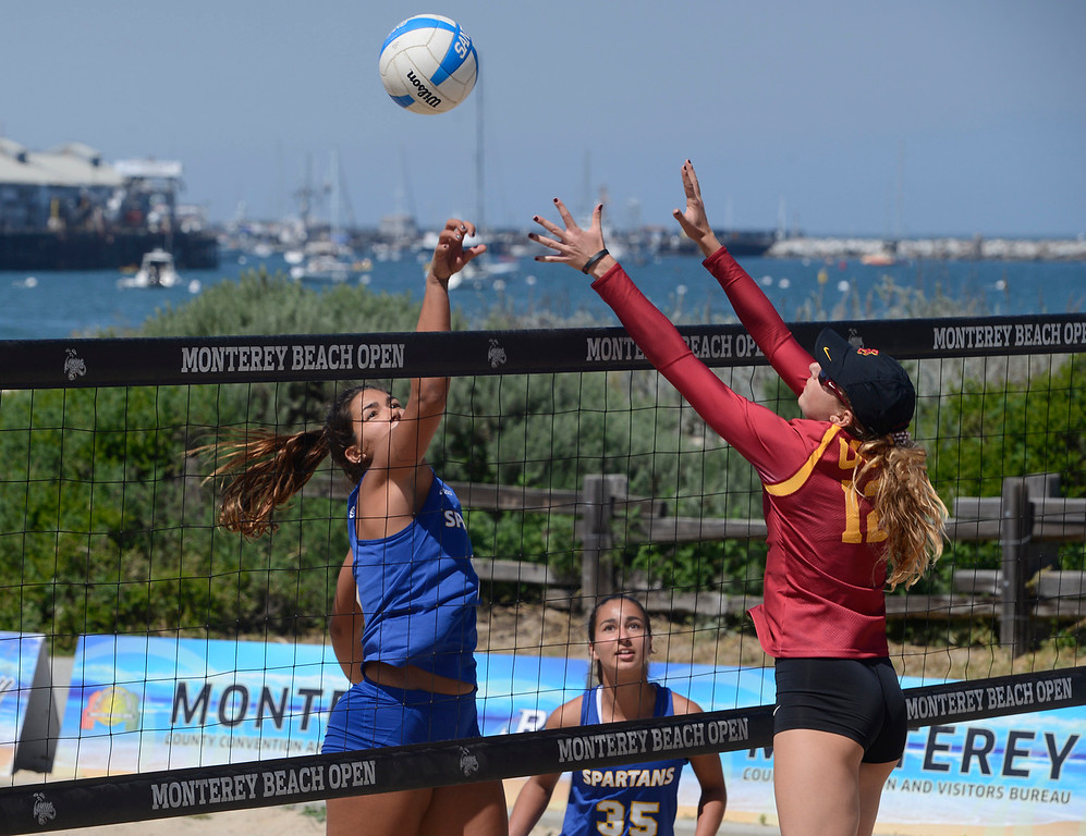 . San Jose State\'s Gulia Gavio, left, hits the ball against USC\'s Allie Wheeler as SJSU\'s Luiza Andrade looks on during the number three match during the second annual Monterey College Invitational beach volleyball tournament at Window on the Bay Park in Monterey on Sunday April 2, 2017. (David Royal - Monterey Herald)