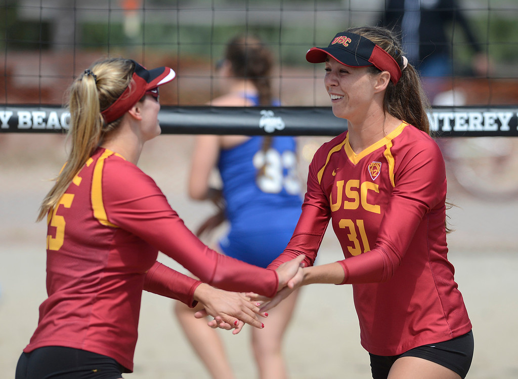 . USC\'s Jenna Belton, right, of Aptos and teammate Jo Kremer hits react after scorring against San Jose State during the second annual Monterey College Invitational beach volleyball tournament at Window on the Bay Park in Monterey on Sunday April 2, 2017. (David Royal - Monterey Herald)