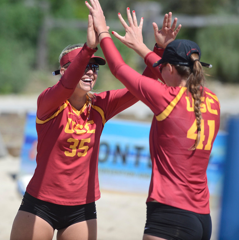 . USC\'s Nicolette Martin, left, and Terese Cannon celebrate a win against San Jose State during the second annual Monterey College Invitational beach volleyball tournament at Window on the Bay Park in Monterey on Sunday April 2, 2017. (David Royal - Monterey Herald)