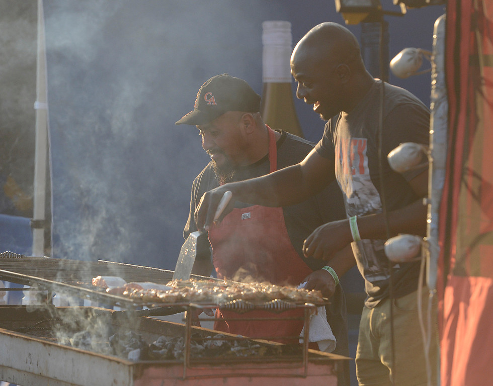 . Martin Estrada and Philip Dah barbeque Salmon and Chicken in the Sankofa BBQ booth during the 59th annual Monterey Jazz Festival at the Monterey County Fair and Events Center in Monterey, Calif. on Friday September 16, 2016.  (David Royal - Monterey Herald)