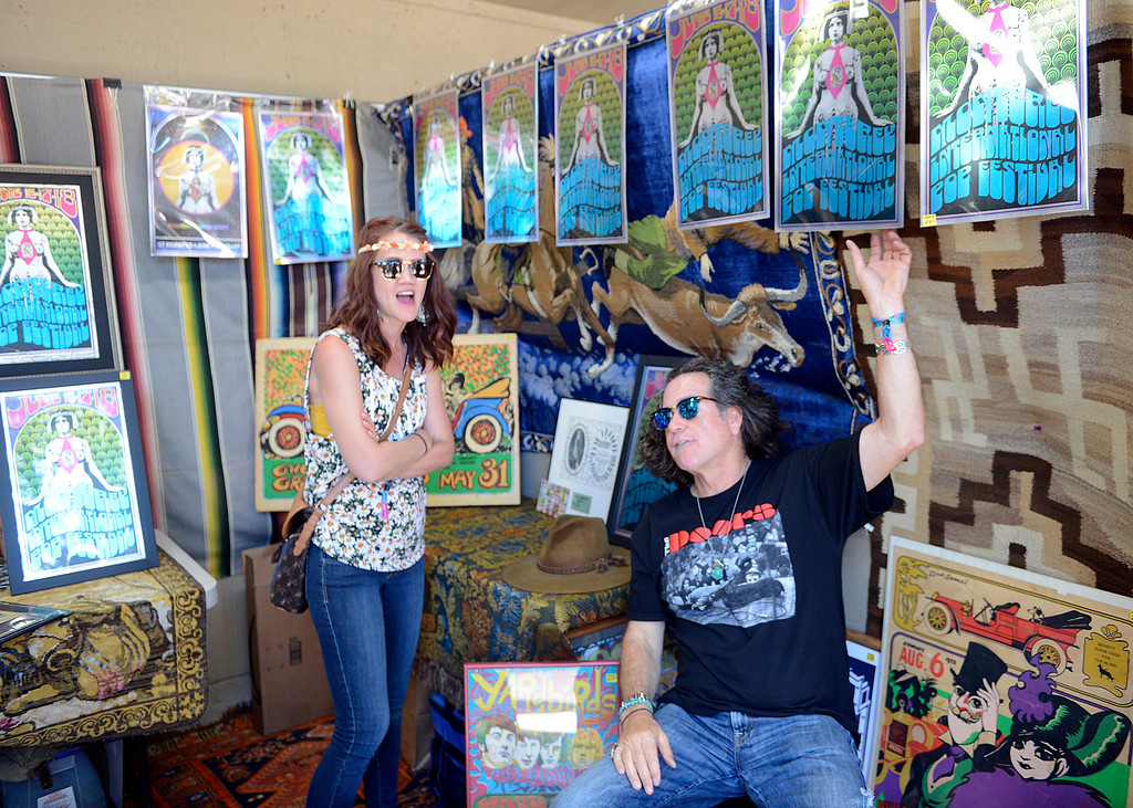 . Scott McAllister points out posters to Evangela Masih while selling art as the Monterey International Pop Festival Celebrates 50 Years at the Monterey County Fairgrounds and Event Center in Monterey on Friday June 16, 2017. (David Royal - Monterey Herald)