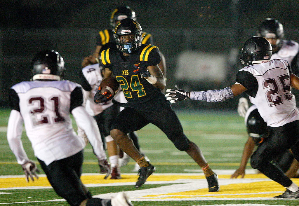 . Monterey High School\'s Timothy Byrd (24) runs for yards in the first-half between Sobrato High School defenders Raymond Valles (21) and Jesse Redmond (25) during their game in Monterey on Friday, September 7, 2018.  (Vern Fisher - Monterey Herald)