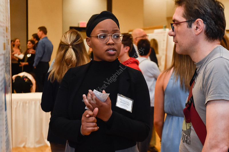 Omosede Irabor, an undergraduate student of the Eberly College of Arts and Sciences presents her research  at the Spring Research Symposium held in the Mountainlair Ballroom on April 13, 2019.