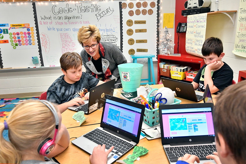 Students in Mrs. Mattern's third grade class room (L to R)  Samantha Laudermilch, Damon Patchen, Gale Manchin West Virginia's Secretary of Education and the Arts,  and Chade Staggs participate in a hour of CODE at Mylan Park Elementary School Morgantown WV December 8, 2017. Photo Greg Ellis
