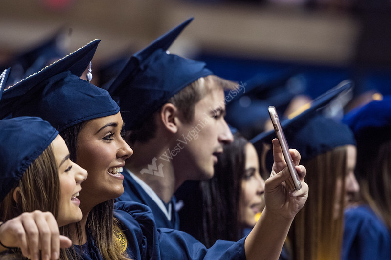 Lydia Boggess, a graudate in Psychology celebrates with a friend on social media during the Eberly College of Arts and Sciences and the College of Business and Economics December Commencement in the Coliseum December 15th, 2017.  Photo Brian Persinger