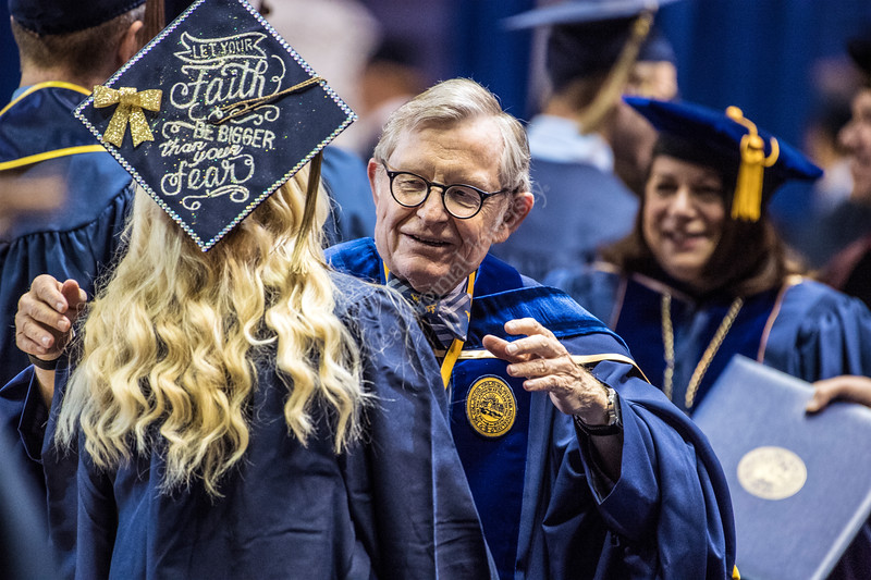President Gordon Gee hugs graduates during the Eberly College of Arts and Sciences and the College of Business and Economics December Commencement in the Coliseum December 15th, 2017.  Photo Brian Persinger