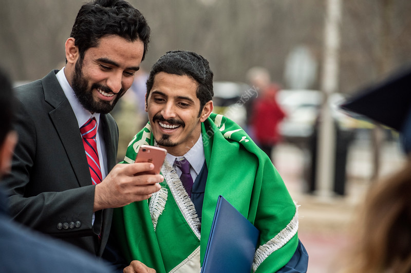 Munahi Alqahtani a Criminology major of Saudia Arabia checks a selfie with a friend after the Eberly College of Arts and Sciences and the College of Business and Economics December Commencement in the Coliseum December 15th, 2017.  Photo Brian Persinger