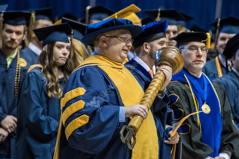 Grand Marshal, Chad Proudfoot processes in with the Mace during the start of the Eberly College of Arts and Sciences and the College of Business and Economics December Commencement in the Coliseum December 15th, 2017.  Photo Brian Persinger