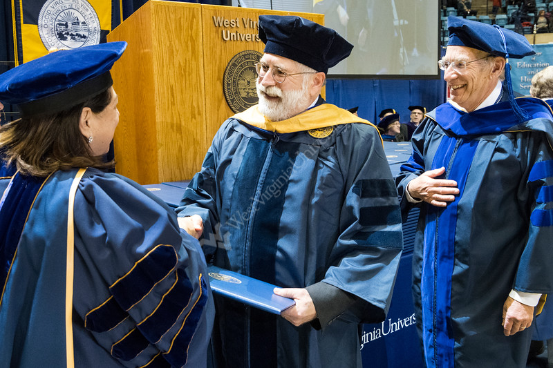 WVU 1983 School of Medicine  graduate Douglas B Learn, PhD walks and receives his diplomat 34 years later from WVU Provost Joyce McConnell, JD, LLM,  as friend Nyles Chardon PhD department of Microbiology  looks on at WVU's December commencement December 15, 2017. Photo Greg Ellis