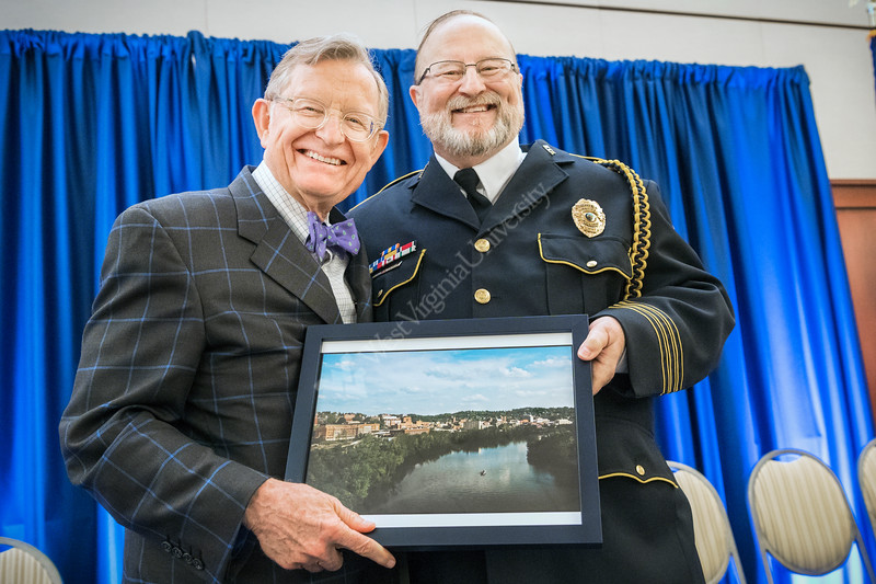 WVU Police Chief of 28 years Bob Roberts  selected 2018 Chief of the Year by the National Association of Campus Safety Administrators, receives a framed photograph of Morgantown WV from WVU President E. Gordon Gee at his retirement ceremony Erickson Alumni Center June 27, 2018. Photo Greg Ellis