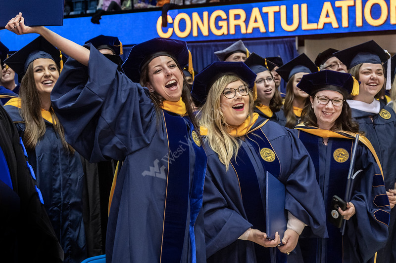 Eberly Graduate students (L to R) Christine Ahaur, Cathelin Clark Gordon and Julia Weiss sing Country Roads at the Eblery May Graduate Commencement, WVU Coliseum May 12, 2019. Photo Greg Ellis