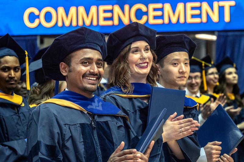 Eberly Graduate students (L to R) Saikanth Gattu, Kristin Kelly and Yu Zhang applaud fellow graduates at the Eblery May Graduate Commencement, WVU Coliseum May 12, 2019. Photo Greg Ellis