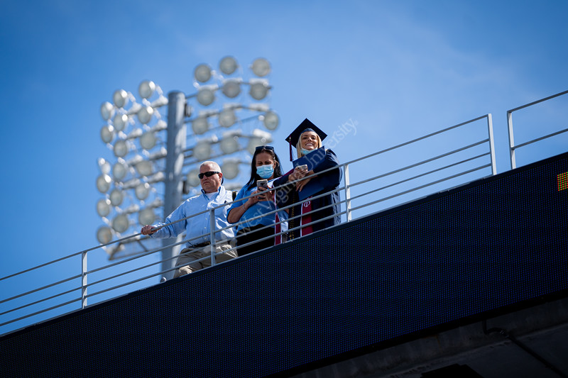 A new WVU graduate smiles while standing on the top level of Milan Puskar Stadium during Commencement, May 15, 2021. Photo: Geoff Coyle