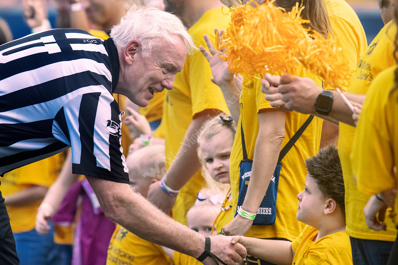 Umpire James Hyson shakes hands with Brantly Poling during a WVU Medicine Children's recognition on Mountaineer Field during the game between the WVU Mountaineers and  NC State Wolfpack September 14th, 2019.  (WVU Photo/Brian Persinger)