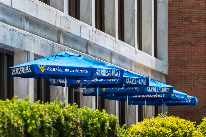 Blue umberellas in front of the WVU  Barnes & Noble book store in the morning sun September2019. (WVU Photo/Greg Ellis)