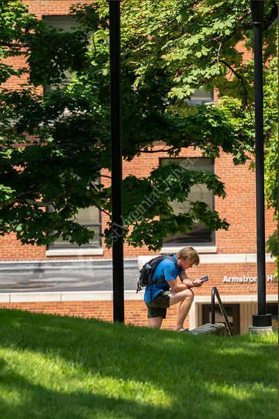A WVU student takes a break in his day checking messages on his phone September 2019. (WVU Photo/Greg Ellis)