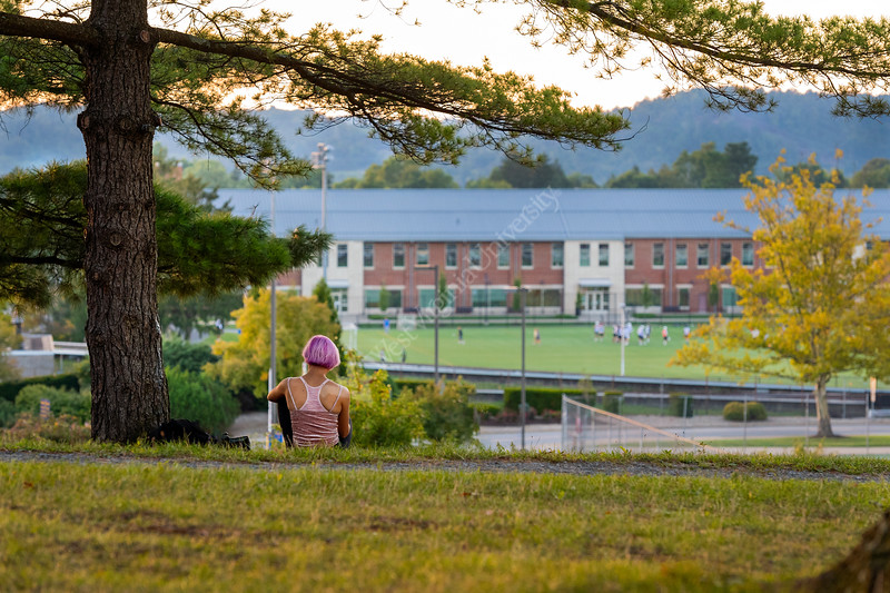 A WVU student takes in the sunset on the Evansdal Campus over looking the WVU Rec field and CPASS College. (WVU Photo/Greg Ellis)