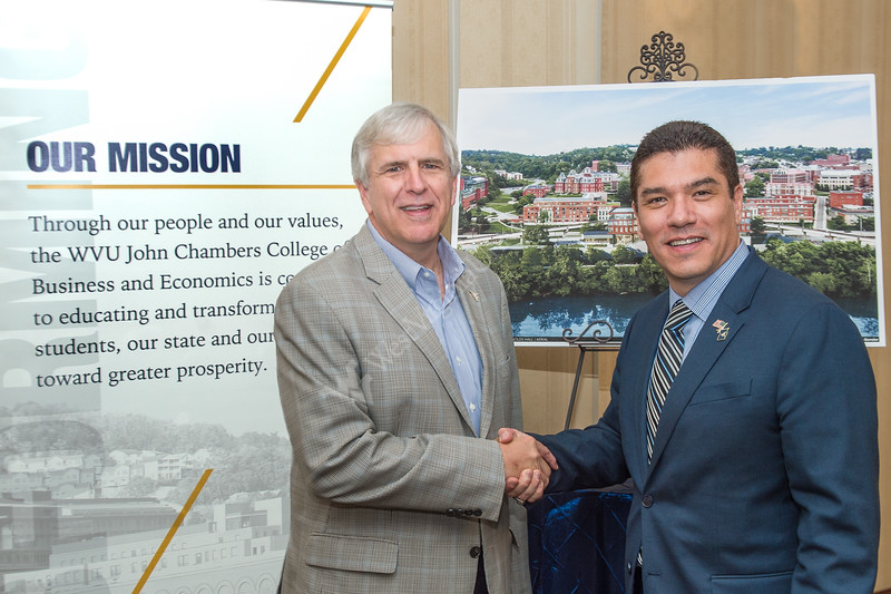 Greg Burton, Executive Chairman of Encova, and Javier Reyes, Dean of the John Chambers College of Business and Economics, greet each other after the announcement of Encova's donation for the construction of Reynolds Halls. The donation is the first to be made by a corporation - announced at the Hilton Garden Inn on September 13, 2019. (WVU Photo/Hunter Tankersley)