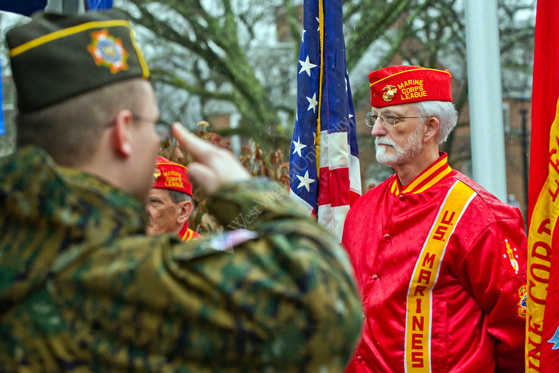 Dewey Nethken of Color Guard, Marine Corps League #342 holds the American flag as a veteran salutes.