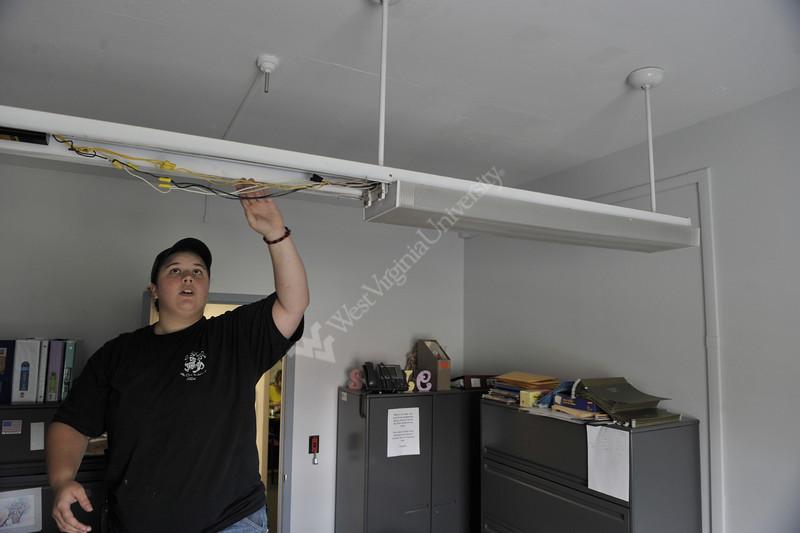 WVU Electrician apprentice Cayla Hefner installs a lighting ballast  as part of her on the job training ,June 2011. (WVU Photo/Brian Persinger)