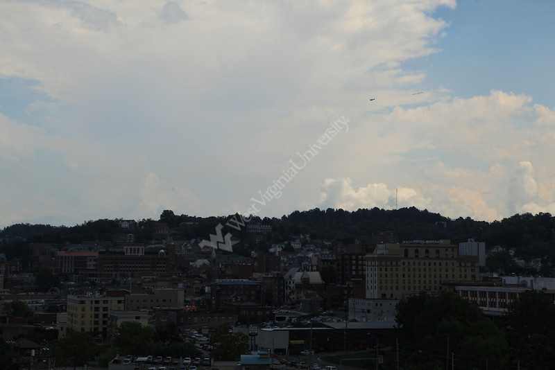 """An airplane flies over downtown Morgantown carrying a banner that reads """"Big 12 loves WVU."""" WVU joined the conference last month and will begin playing Big 12 football games next month."""