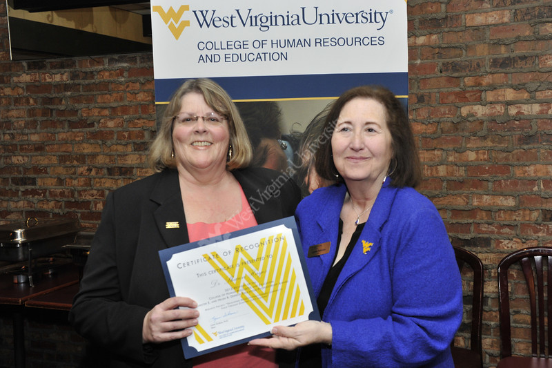 WVU HRE Dean (right) poses for a photo presenting an award at the WVU Capital Classic Charleston WV December 2012. (WVU Photo/Greg Ellis)