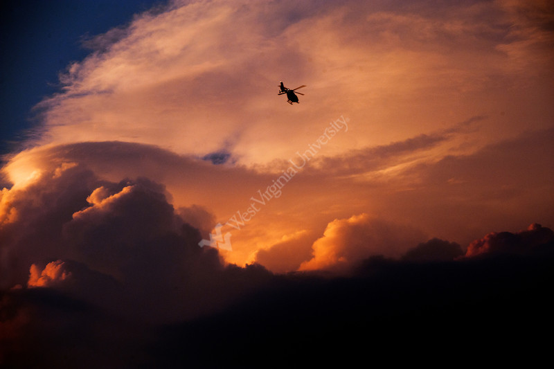 A helicopter flies in the clouds and evening sun over the WVU campus. June 2012 (WVU Photo/Brian Persinger)
