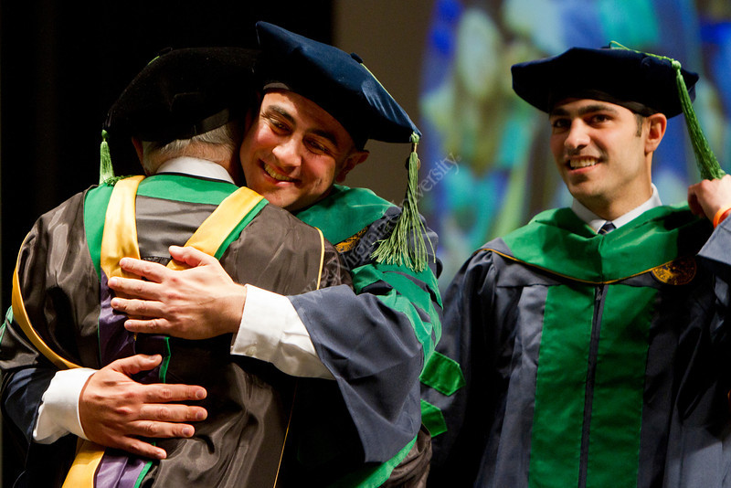 Mark Tarakji hugs his father as his brother looks on from the right. Tarakji received a Doctor of Medicine degree at the WVU School of Medicine's 2012 Commencement ceremony.