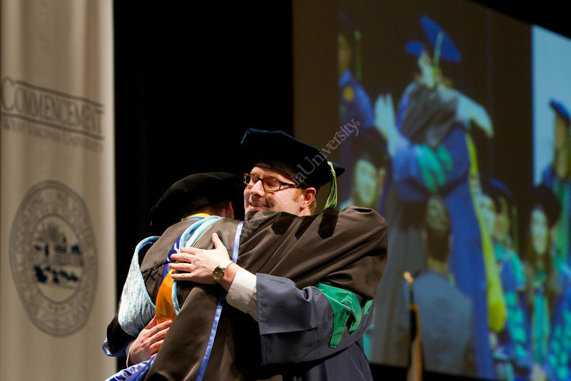 Templeton Smith III hugs a faculty member after receiving his degree at the WVU School of Medicine's 2012 Commenecment ceremony.