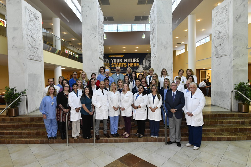The Department of Obstetrics and Gynecology pose for a group photograph by the pylons at the Health Sciences Center August 15th, 2018.  Photo Brian Persinger