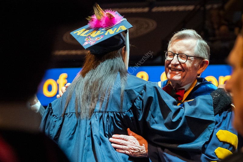 Alayna Fuller shares a moment with WVU President E. Gordon Gee along with other WVU graduates from the Eberly College of Arts and Science and the John Chambers College of Business and Economics convene with their families and faculty for the December 2018 Commencement at the WVU Coliseum , December 12, 2018. Photo Greg Ellis